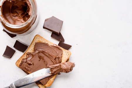 Chocolate-nut paste spread toast on light background with copy space top view.