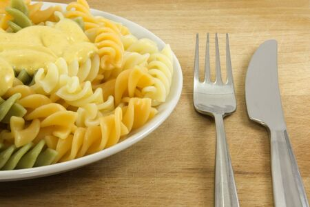 gastronome: Close-up fork and knife with coloured pasta with sauce