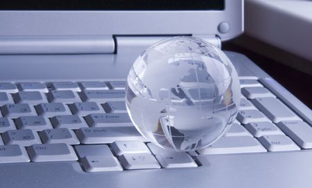 Crystal-glass globe on keyboard of  modern notebook. Background photo
