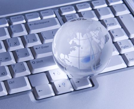 Crystal-glass globe on keyboard of notebook. Background photo