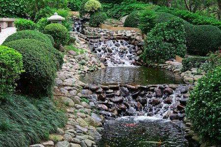 Waterfall ad pond with goldfishes in japanese garden photo