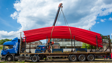 Crane unloading track fully loaded with red plastic tubes