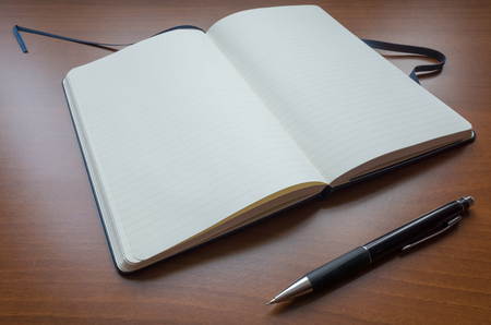 Blank paper notebook and Pencil on brown wooden table background 版權商用圖片