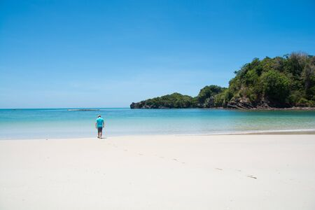 man walking on beautiful beach and tropical sea at lipe island ,satun Thailand