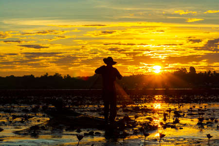 A fisherman catching freshwater fish during on sunsrise. Silhouette.