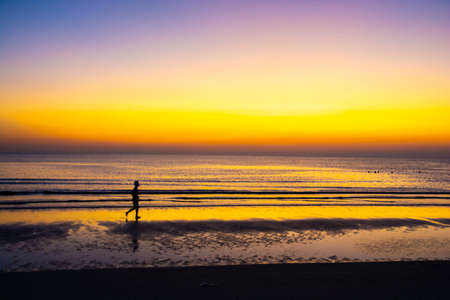 Man relaxing on the beach at sunrise, beautiful cloudy sky