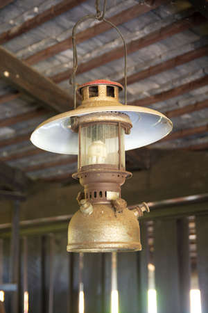 Old oil lamp hanged on a roof of house.
