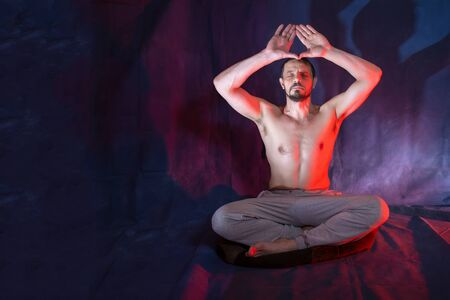 A man sits in a lotus position. Male European 40-45 years old. A man is engaged in meditation. The man raised his arms above his head. Magic and occultism.