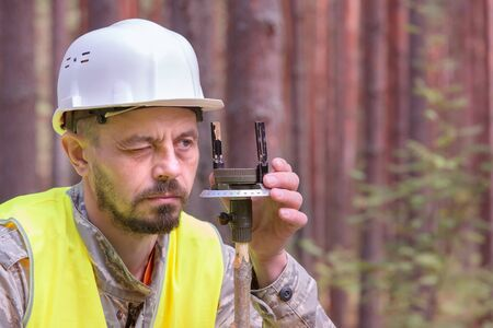 Forest engineer works in the forest with a compass. White helmet and yellow vest. Forestry. Real people work.