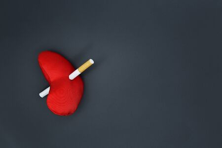 The concept of harm from smoking cigarettes. Cigarette. dark background. A red heart pierced a cigarette. 版權商用圖片