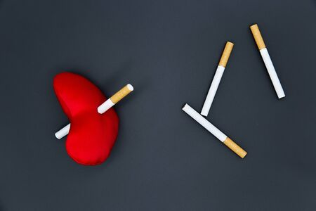 Cigarettes on a black background. A red heart is killed by a cigarette. Diseased heart. The harm of smoking.