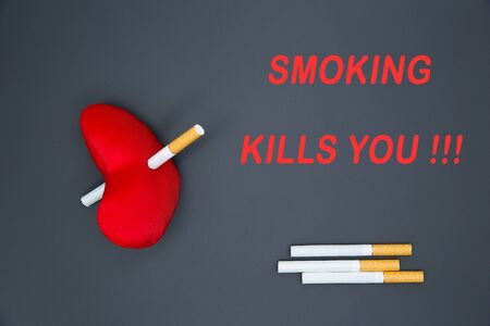 The inscription on a black background: Smoking kills you !!! Cigarettes are scattered, a heart broken by a cigarette. Harm from smoking cigarettes.