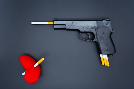 Gun barrel and cigarette. Heart killed by a cigarette. The concept of harm from smoking.
