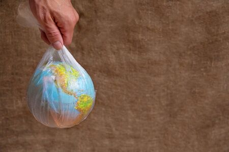 Globe in a plastic bag. The hand carries the globe. Earth drowned in plastic. Plastic pollution.