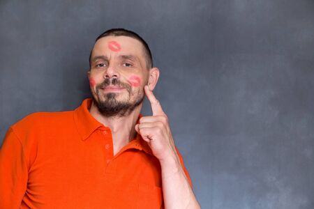 A man with traces of kisses. Shows a finger. 40 year old man in lipstick. Blue background, bearded man.