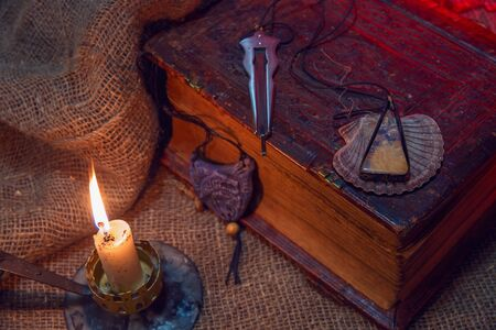 Old book and rough cloth. The musical instrument of the harbor lies on the book. Semiprecious stone lies on the book. A bright candle burns. The concept of occultism and magic.
