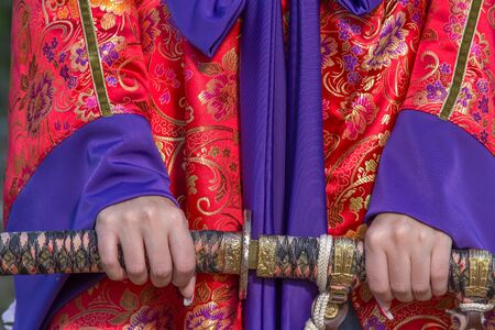 Female hands hold a sword. Chinese national clothes.