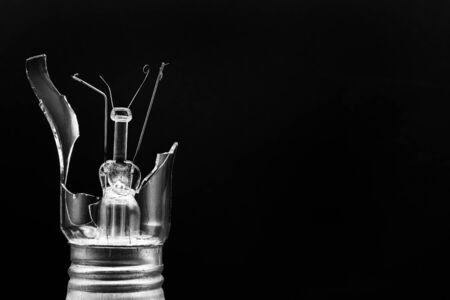 Broken incandescent lamp. Glass shards. The glass shatters to the sides. The sharp edges of the glass. Black background. Advertising concept.