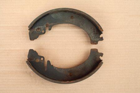 Old brake pads lie on a cardboard sheet.