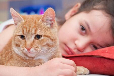 A girl of European appearance hugs a cat and smiles. Portrait of a girl with a red cat. Relations between children and pets.
