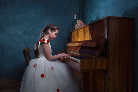 A girl plays the piano. Baby girl in a beautiful dress. Red cat is sitting on the piano. The candle is burning.
