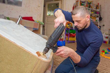 A European man repairs furniture in his house.