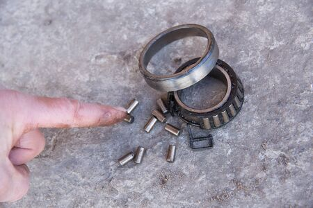 Finger points to the destroyed bearing. Old bearing and rollers are lying on concrete. Low-quality spare parts for the car. The reason for the breakdown of the car.