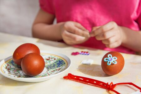 Easter eggs are in the plate. The painted egg lies on the table. Children's hands decorate Easter eggs. Reklamní fotografie
