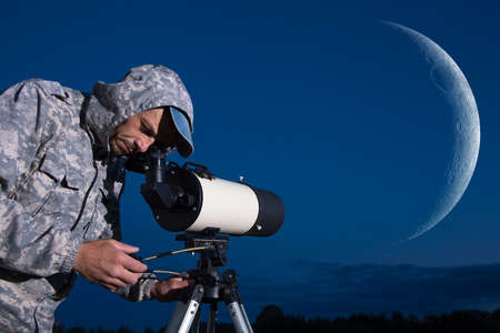 A European man is watching the moon through a telescope. Amateur astronomer.
