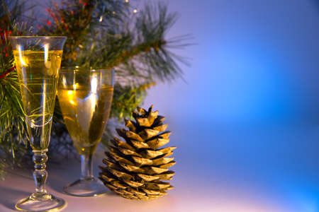 Christmas background. Spruce green branches. New Year's toys hang on fir branches. Glasses with a drink. Beautiful colored lighting.