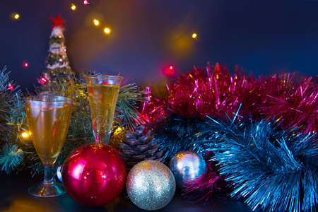 Christmas background. Branches of the New Year's spruce. New Year's toys. Glasses with a drink. Beautiful colored lighting. Toy Santa Claus.