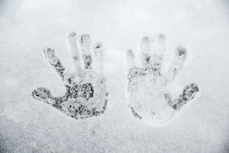Handprints in the snow. The concept of the onset of winter and cold weather.