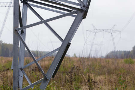 High-voltage electricity transmission line in the background. Metal structure, close-up photo. Cloudy sky, wires.
