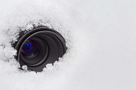 The camera lens is hidden in the snow. Covert video surveillance concept.