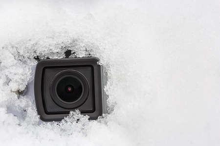 The camera lens  hidden in the snow. Covert video surveillance concept.