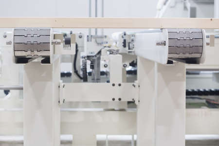 Glued laminated timber lies on the conveyor belt of a woodworking machine. Automated line. Constructional building materials made of wood. Woodworking industry concept.