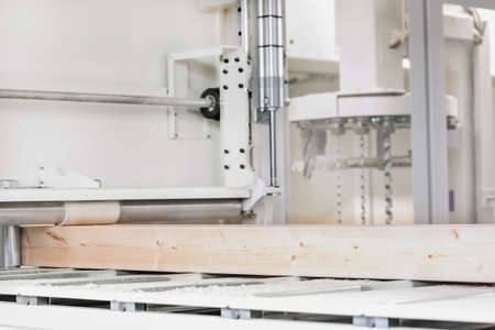 Glued laminated timber lies on the conveyor belt of a woodworking machine. Woodworking industry concept.