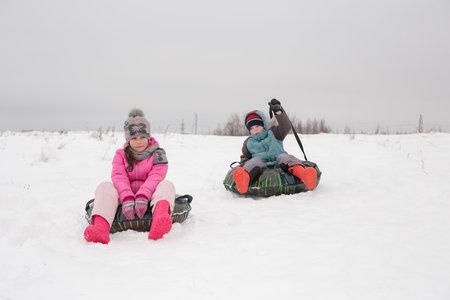 孩子们坐在幻灯片上芝士蛋糕。在一个女孩的选择聚焦桃红色夹克的。在无人居住的地方户外散步的概念。