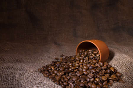 Coffee beans are poured out of a clay cup onto a rough canvas. Selective focusing on grains. A photo with a shallow depth of field.