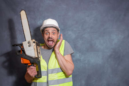 A European man with a chainsaw. A worker with a chainsaw is surprised and screams. A bright emotion of surprise.