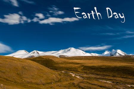 Snowy peaks of crust against the blue sky. Earth Day inscription.