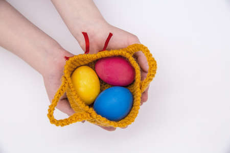 Children's hands are holding colored Easter eggs.