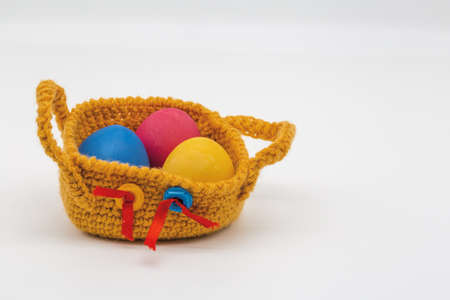 Painted eggs lie in a knitted basket.