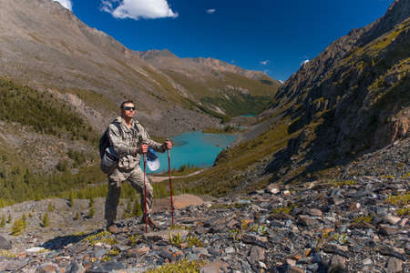 Male traveler on the background of high snow-capped mountains.