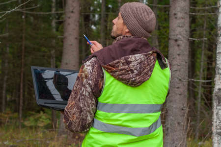 Forest engineer works in the forest with a computer. Digital technologies in forestry. Computer forest inventory.