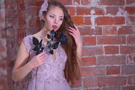 A young woman in a pink dress holds a black rose in her hands. A girl in a destroyed building. Red brick.