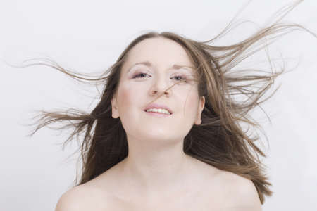 flying hair: Smiling girl with flying hair looking straight Stock Photo
