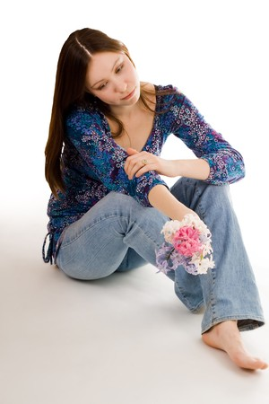 bulbar: Romantic woman siting on the flor with flowers in hand looking down Stock Photo