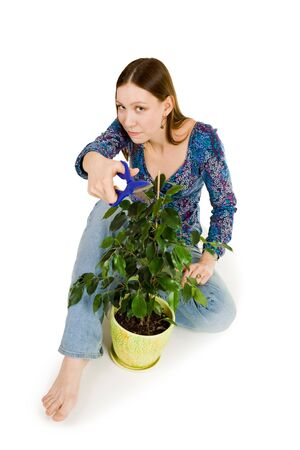 horticulturist: Woman sitting on the flor and pointing at you with scissors Stock Photo