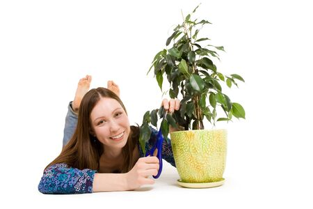 Woman laying on the floor cutting plant with scissors photo